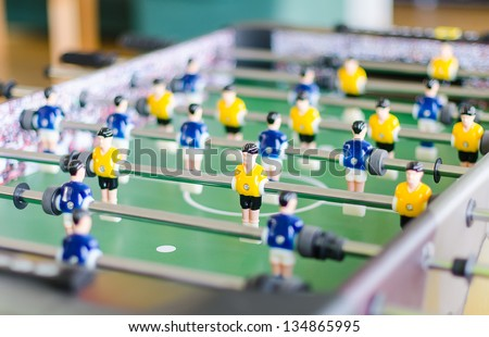 Table football game with yellow and blue players - stock photo
