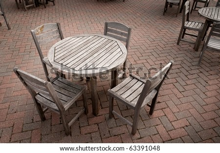 Table for Four - Groups of tables and chairs on brick patio - stock photo