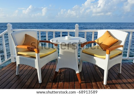 Table for two in water bungalow close to the ocean - stock photo