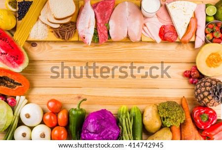 table full of all kinds of food in our daily diet includes proteins, carbohydrates, fats, vegetables and fruits - stock photo