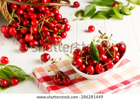Table full of fresh red cherries, cherries in the bowl and cherries spilled from the basket - stock photo