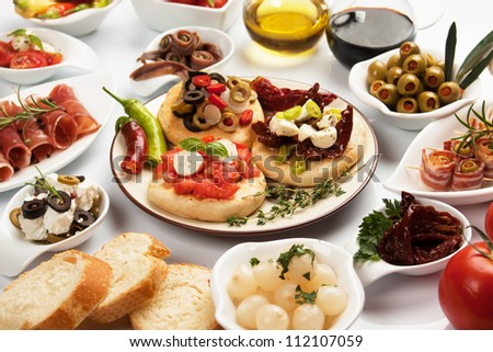 Table full of mediterranean appetizers, tapas or antipasto - stock photo