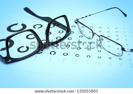 Table Golovin and glasses eye tests on a blue background. - stock photo