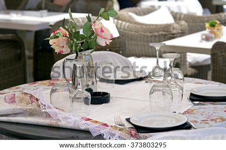 table in a cafe, serving table in a cafe, Empty outdoor restaurant table, Empty glasses in restaurant, dwarf tree on a table in a cafe, roses in the vase on table - stock photo