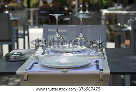 table in a cafe, serving table in a cafe, Empty outdoor restaurant table, Empty glasses in restaurant, dwarf tree on a table in a cafe, roses in the vase on table, table in a cafe with roses - stock photo