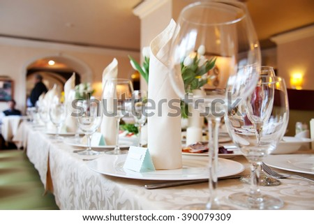 Table in a restaurant with glasses, napkins and cutlery - stock photo