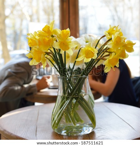 Table in the cafe with lent lily and loving couple at background. Date. Urban lifestyle. Image toned. - stock photo