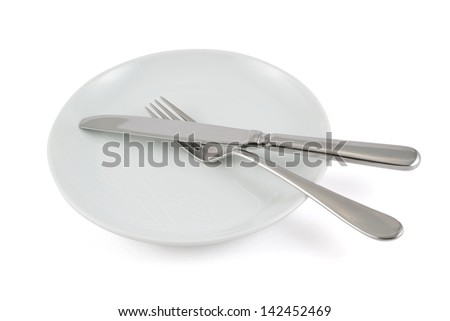 Table knife and fork over ceramic empty copyspace plate dish isolated over white background