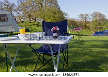 Table laid for breakfast alfresco on campsite in Wales, UK. - stock photo