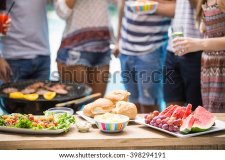 Table laid with hamburgers, fruits and barbecue for outdoors barbecue party - stock photo