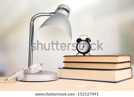 Table lamp and books on desk in room