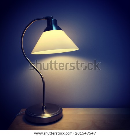 Table lamp on a wooden surface, in a dark room. - stock photo