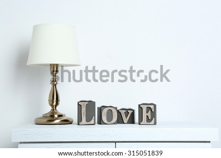 Table lamp with word Love on wall background - stock photo