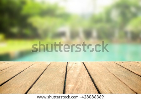 Table near the pool at sunny vacation day - stock photo