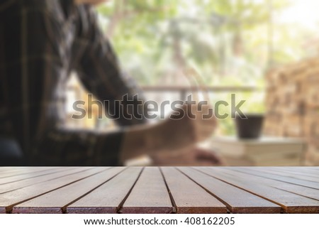 table of free space and man reading book in library .Retro filter effect,soft focus,low light.(selective focus)  - stock photo