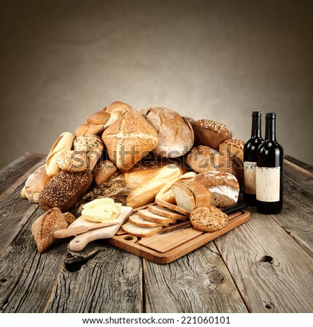 table of fresh bread and two bottles of wine  - stock photo