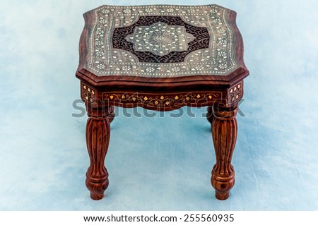 Table of India . Rosewood , carved , inlaid brass .