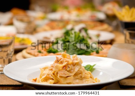 Table of pasta and other food plates in the background  - stock photo