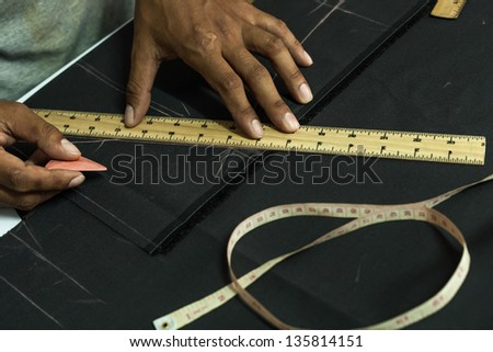 Table of skilled tailors working. - stock photo
