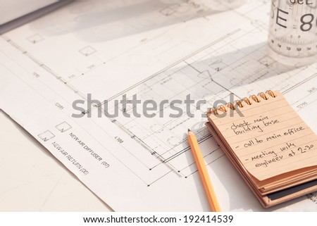Table of the architect with notebook and a blueprint of the house - stock photo