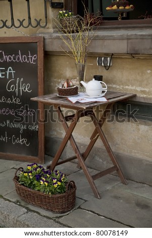 Table on a summer terrace with cake and teapot. - stock photo