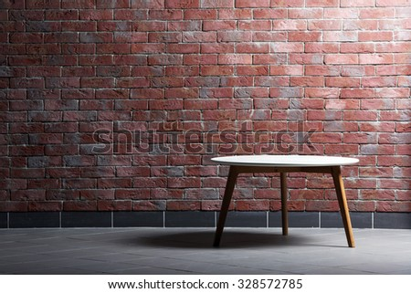 Table on brick wall background - stock photo