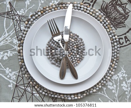 Table place setting with African beaded place mats - stock photo
