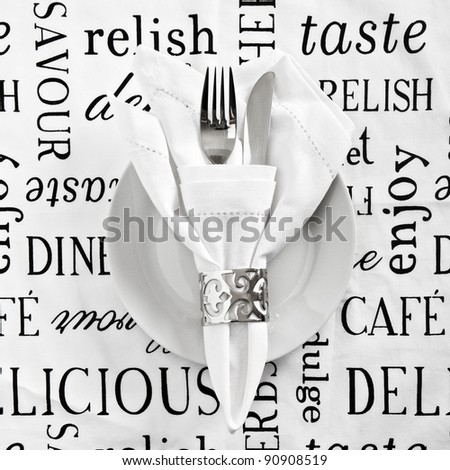 Table place setting with printed white linen - stock photo