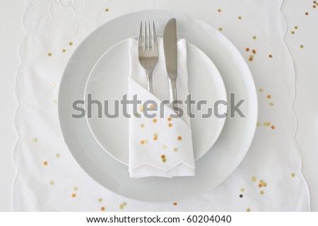 Table place setting with white linen and gold stars for a Christmas theme - stock photo