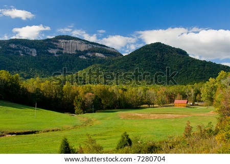 table rock mountain fall scenic with mountain meadow and distant peak - stock photo