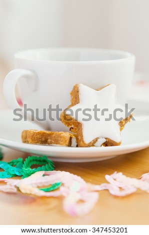 Table served to tea drinking. White cup of tea, star cake and Christmas decoration on the wooden table. - stock photo