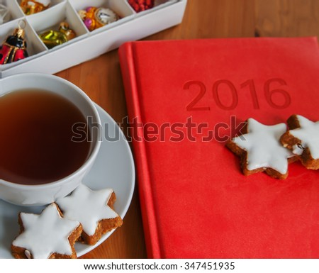 Table served to tea drinking. White cup of tea, star cake, diary for 2016 year  and Christmas decoration on the wooden table. - stock photo