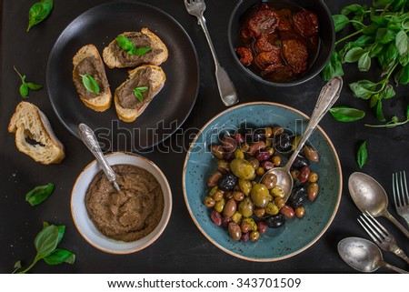 Table served with bread, tapenade, assorted olives, dried tomatoes in olive oil and basil. Dinner table with french provence appetizers and canapes - stock photo