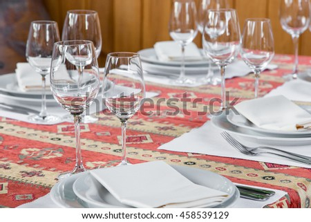 Table served with dishes, close up. Ethnic table cloth, served with glasses, plates and cutlery