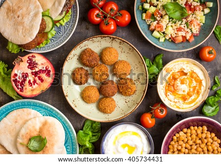 Table served with middle eastern traditional dishes. Bowl with falafel, doner kebap, vegetarian pita, hummus, tabbouleh bulgur salad, chickpea, olive oil dip, pomegranate. Top view. Dinner party - stock photo