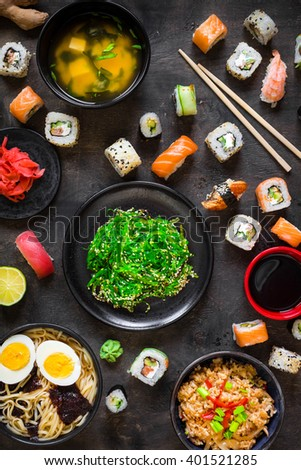 Table served with sushi and traditional japanese food on dark background. Sushi rolls, hiyashi wakame, miso soup, ramen, fried rice with vegetables, nigiri, soy sauce, Chopsticks. Overhead     - stock photo