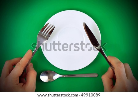 Table serving-knife, fork  in hands on green  background.Spotlight source on top and in center.
