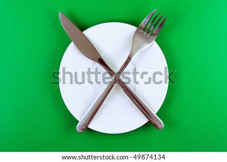 Table serving- knife, spoon, fork   on  green   background.