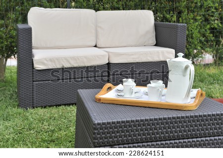 Table set and green garden furniture outdoor ready to enjoy tea time or coffee. - stock photo
