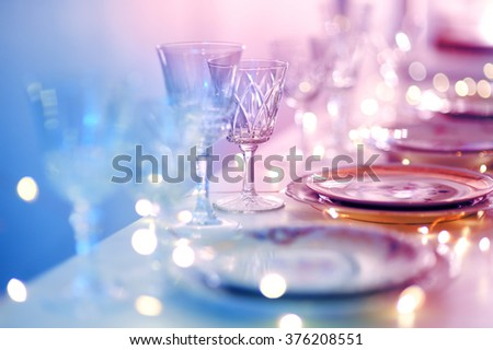 Table set for an event party or wedding reception in purple light - stock photo