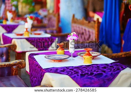 Table set for dinner in traditional Moroccan street restaurant - stock photo