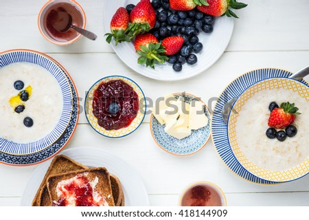 Table set for Tasty Family Breakfast with Toasts, Butter, Raspberry Jam, Oat Porridge, Strawberries, Blueberries on White Background, selective focus - stock photo