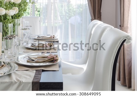 table set on dark brown wooden table in dinning room with white chair - stock photo
