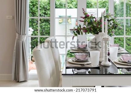 table set on glass dinning table with white chairs at home