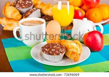 Table set up for breakfast: coffee, egg, pastry, fruits.