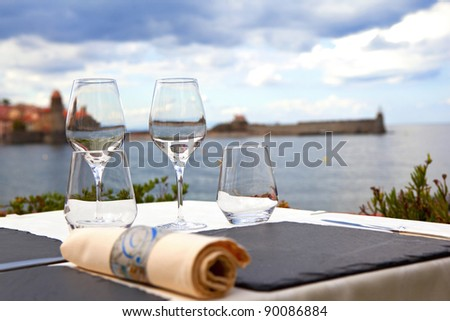 Table set up on the terrace of a restaurant by the sea
