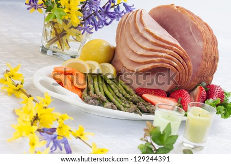 Table set with festive glazed ham for Easter celebration dinner garnished with asparagus, carrots, strawberry, and lemon wedges. - stock photo
