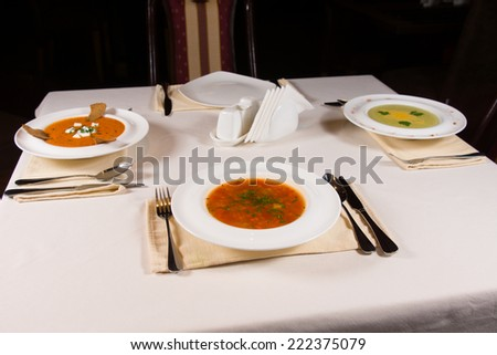 Table set with three different bowls of gourmet vegetable soup with artistic plating in white bowls for an appetizer to a formal dinner - stock photo