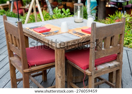 table setting and eating concept - close up of cutlery with glass and napkin on restaurant table - stock photo