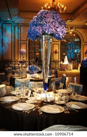 Table setting at a luxury wedding reception in a large ballroom
